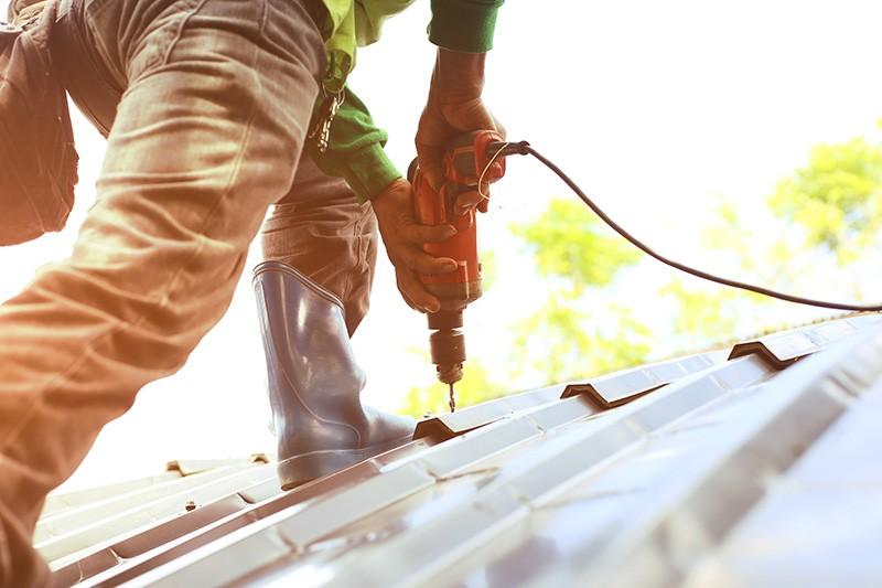 man on roof restoring roof