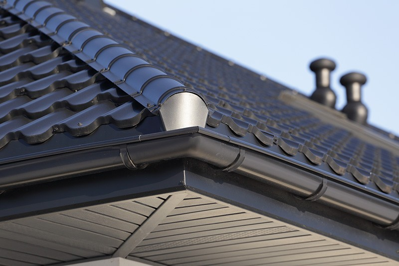 corner of a roof with black gutter guards