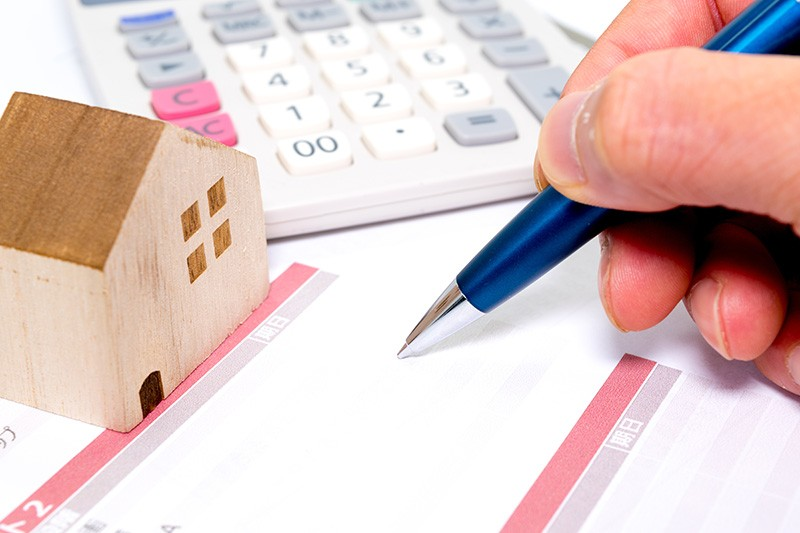 person calculating cost of home with pen and paper and calculator